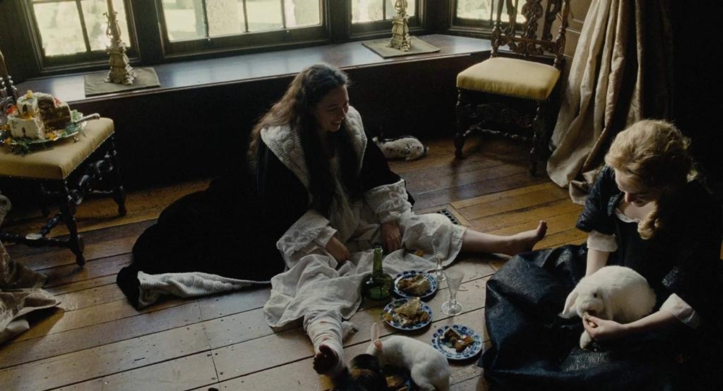 Dronning Anne (Olivia Colman) og Abigail (Emma Stone) hygger sig i selskab med Annes nuttede, mystiske kaniner. (Foto: IMDB)