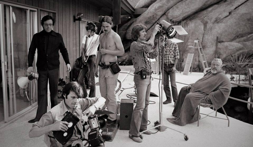 Orson Welles under optagelserne til The Other Side of the Wind (2018). Han sidder længst til højre iført badekåbe. (Foto: Netflix/José María Castellví)