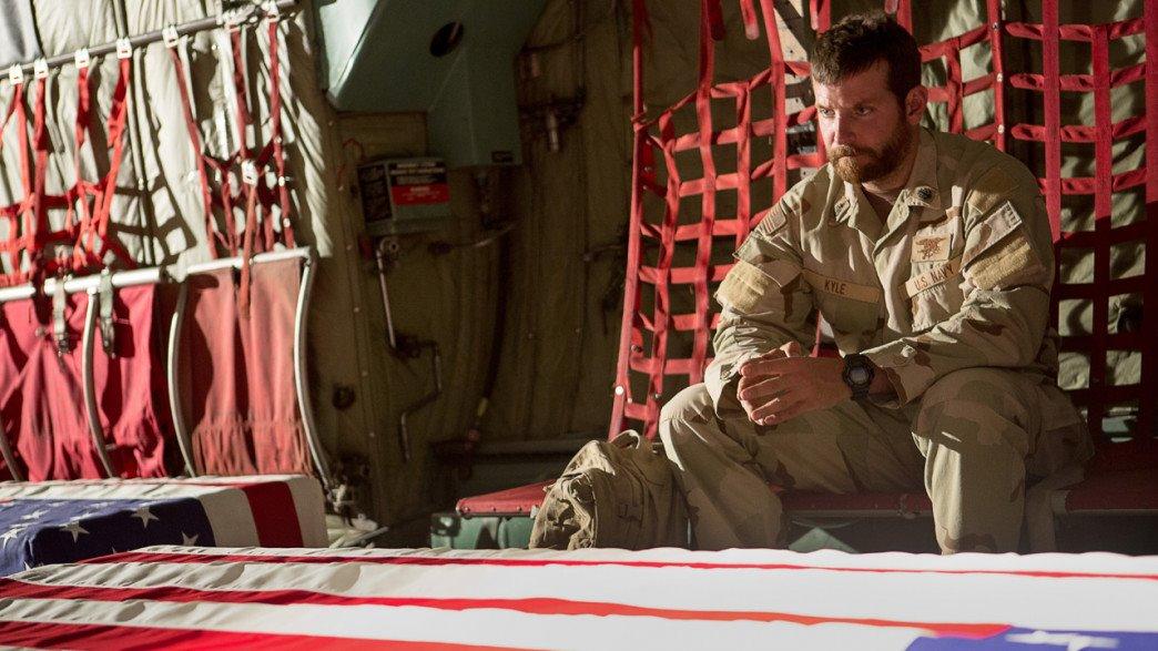 Kyle (Bradley Cooper) stirrer på kameraternes kister, der sendes hjem fra slagmarken. (American Sniper (2015) Foto: Warner Bros.)